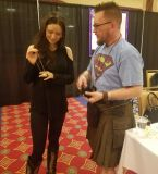 Summer Glau holding a Wonder Woman necklace from Caped Justice Jewelry